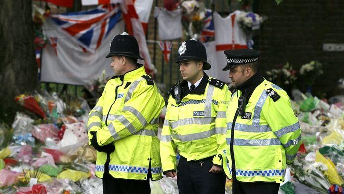 Britse agenten bij de duizenden bloemen op de plaats waar de militair Lee Rigby werd vermoord.