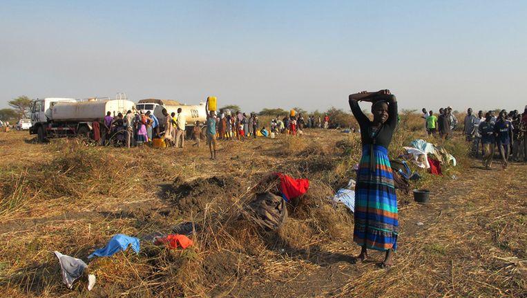 VN-medewerkers delen water uit aan de vluchtelingen in Zuid-Soedan. Beeld AFP PHOTO / UNMISS / Anna Adhikari