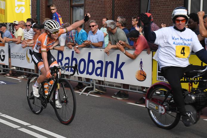 Anna van der Breggen steekt een arm in de lucht na haar zege in Boxmeer, haar dernyrijder juicht mee.
