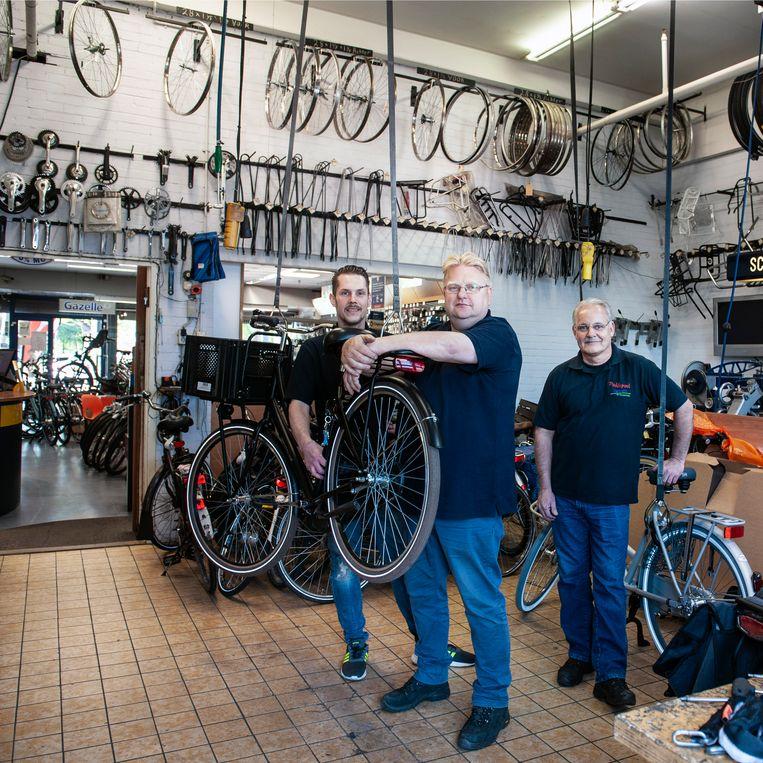 Peter Oest (midden) en Martin Haijkens (rechts) met een medewerker van Paddepoel Fietsen in hun werkplaats. Beeld reyer boxem