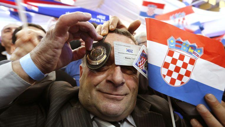 Een aanhanger van de HDZ viert de overwinning van zijn partij. Beeld epa