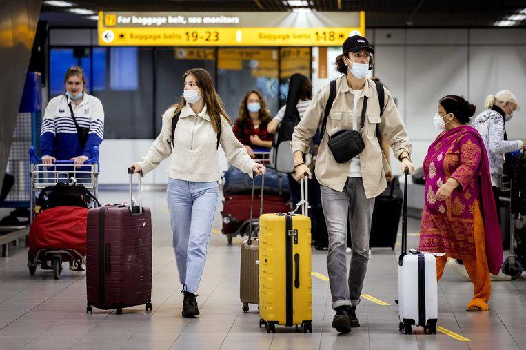 Reizigers met mondkapjes op luchthaven Schiphol. Beeld ANP