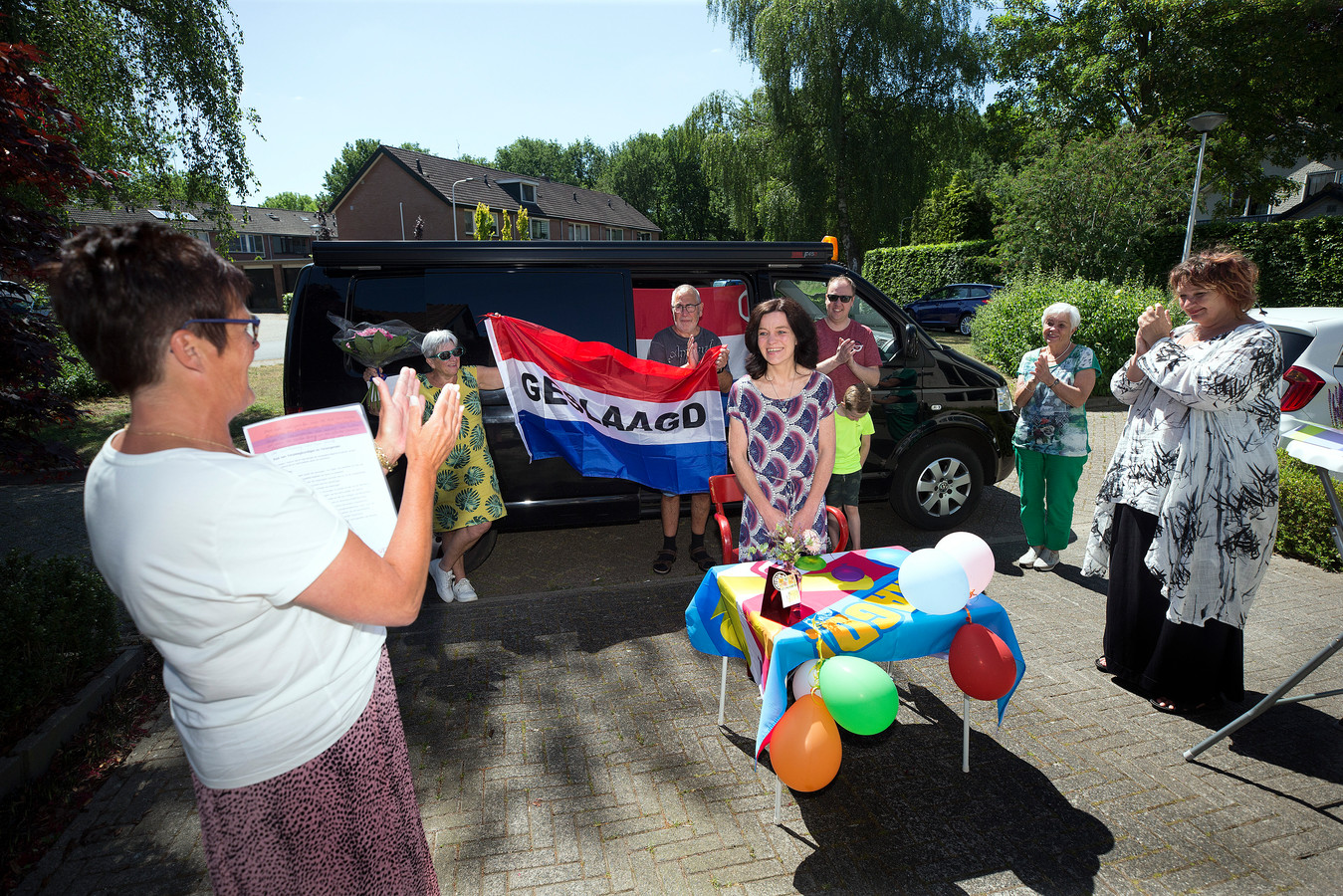 Adinda van der Linden uit Groenlo is maar wat blij met haar diploma. De uitreiking vond plaats op de parkeerplaats voor haar huis.