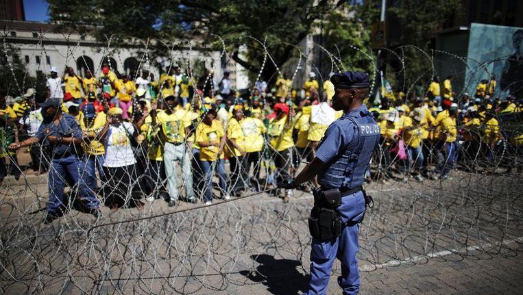 De Zuid-Afrikaanse politie spant prikkeldraad tegenover ANC-demonstranten Beeld ANP