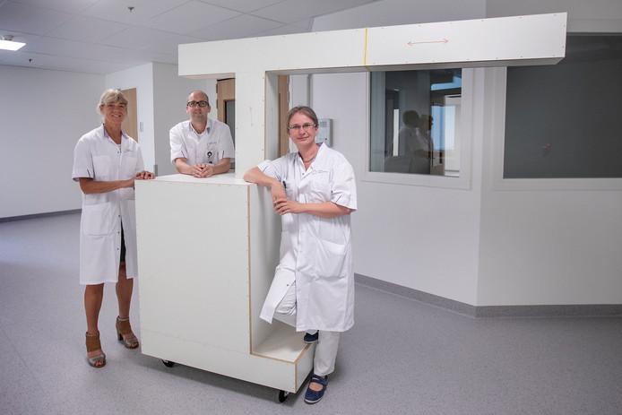 Marlies Bongers,  Kevin de Laet en Joleen Blok (vlnr) bij het houten model van een van de drie  robotarmen. Het model wordt gebruikt om de plaatsing in de operatiekamer te bepalen. Foto Kees Martens/fotomeulenhof