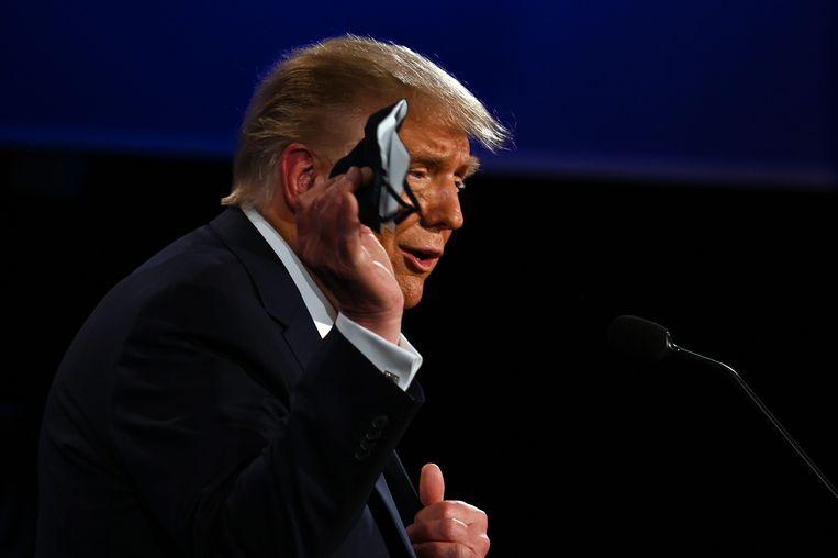 President Trump op 29 september, tijdens het eerste presidentiële debat, met in zijn hand een mondkapje.  Beeld AFP