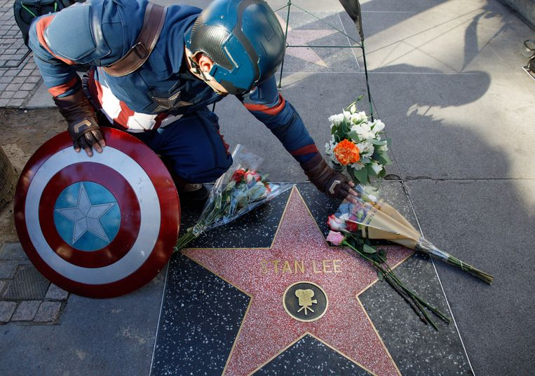 Een als Captain America verklede man raakt de bloemen aan die ter herinnering aan de op 12 november overleden Stan Lee zijn neergelegd op de Walk of Fame in Hollywood, Californië.  Beeld null