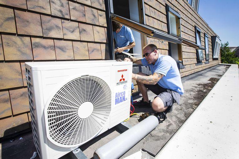Een installateur plaats een airconditioner in een woning in Hooglanderveen. Beeld ANP