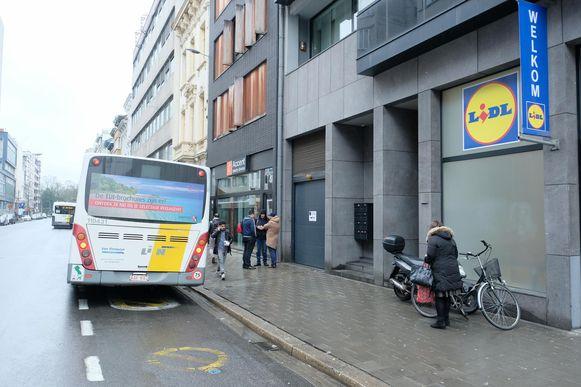 Een bus van De Lijn staat met draaiende motor stil op het fietspad.