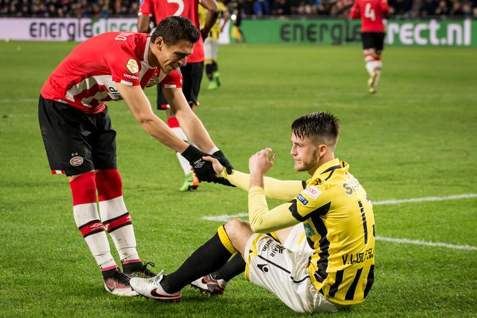 Ricky van Wolfswinkel wordt overeind geholpen door Hector Moreno van PSV.