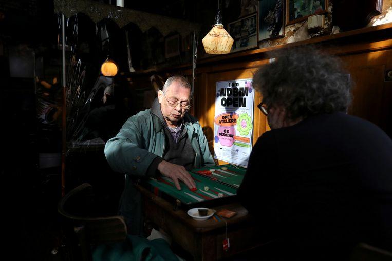 Bezoekers spelen een bordspelletje voordat de cafés worden gesloten. Beeld REUTERS