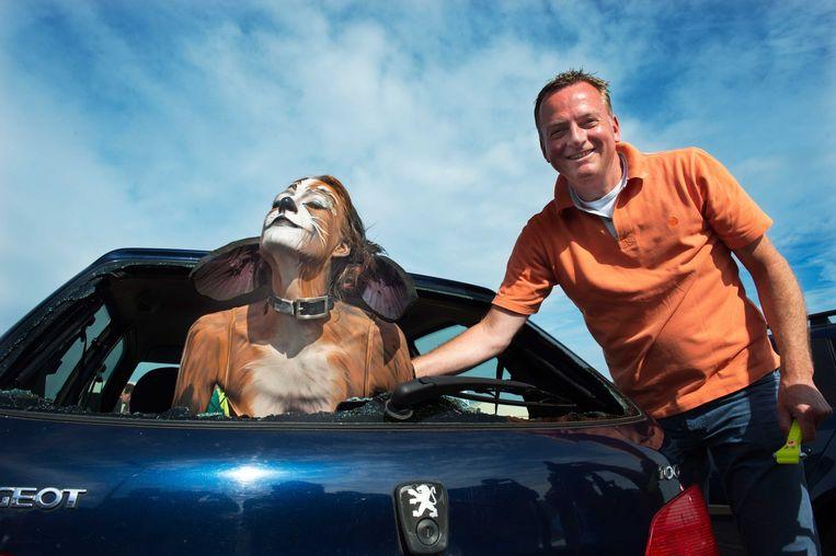 Directeur Frank Dales van de Dierenbescherming bevrijd na het intikken van een auto ruit een 'hond' uit een auto. De Dierenbescherming wilde in 2012 met deze actie een oproep doen om alert te zijn op honden die achtergelaten zijn in geparkeerde auto's. Beeld anp