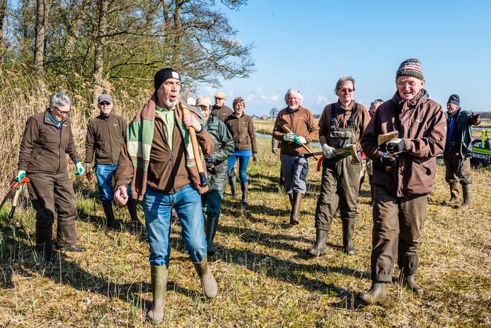 Een groep vrijwilligers van Natuurmonumenten betreedt een gebied waar ze met bijlen en zagen aan de gang kunnen gaan.