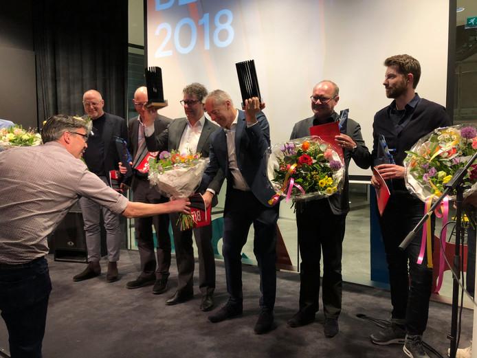 Hein van Bommel (midden, met trofee) neemt als winnaar de bloemen in ontvangst.