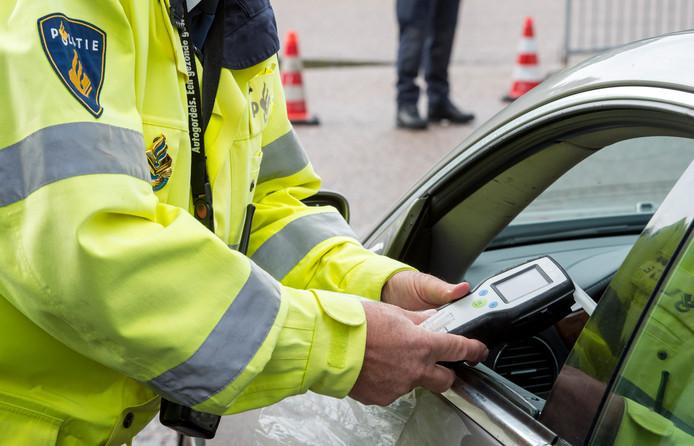 Een politieagent neemt een blaastest af.