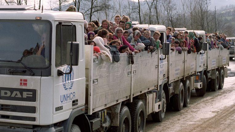 Archieffoto uit 1995 waarop te zien is hoe moslimvluchtelingen op VN-trucks de stad Srebrenica uit rijden. Beeld epa