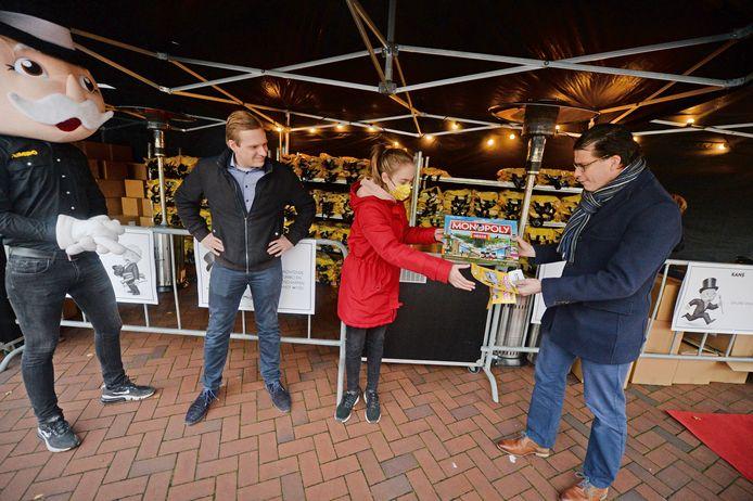 Burgemeester Joost van Oostrum krijgt uit handen van Julia van der Linde het eerste exemplaar van de Needse editie van gezelschapsspel Monopoly. Links supermarktdirecteur Tijn Leussink en Jordie Wegerink als Mr Monopoly.