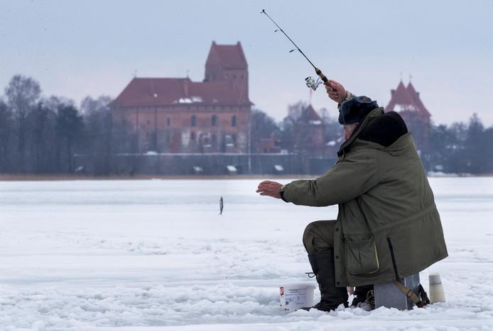 Een visser haalt zijn vangst omhoog op het met sneeuw bedekte Galve-meer in Trakai, in Litouwen. Foto Mindaugas Kulbis
