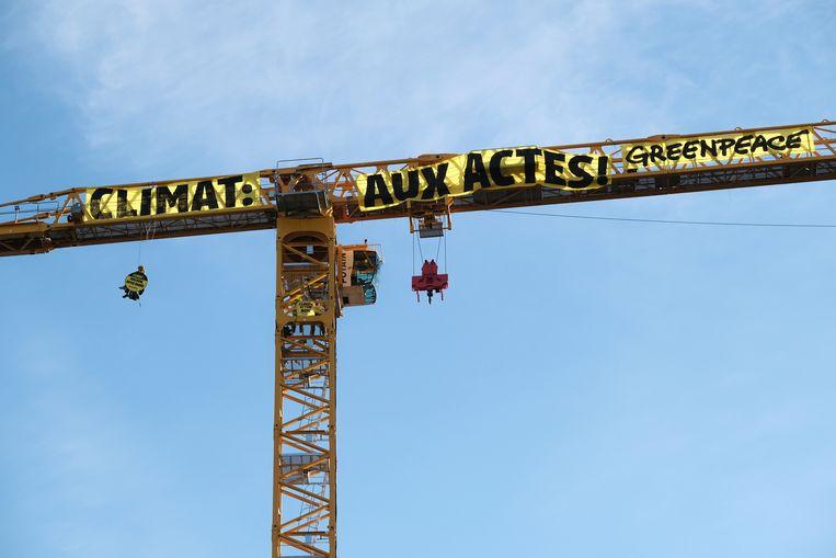 Greenpeaceactivisten beklimmen hijskraan bij de Parijse kathedraal Notre-Dame en hangen spandoek op.