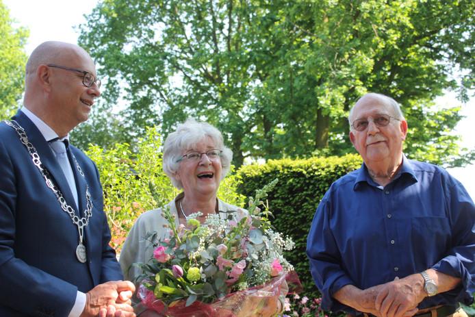 Wethouder Gerard Bruijniks (links) verrast het diamanten echtpaar met bloemen en een taart.