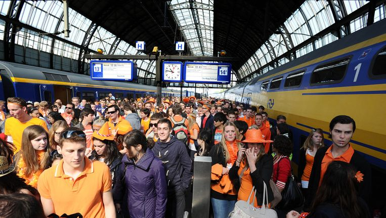 Oranje uitgedoste feestvierders komen op Amsterdam CS. Archieffoto. Beeld ANP