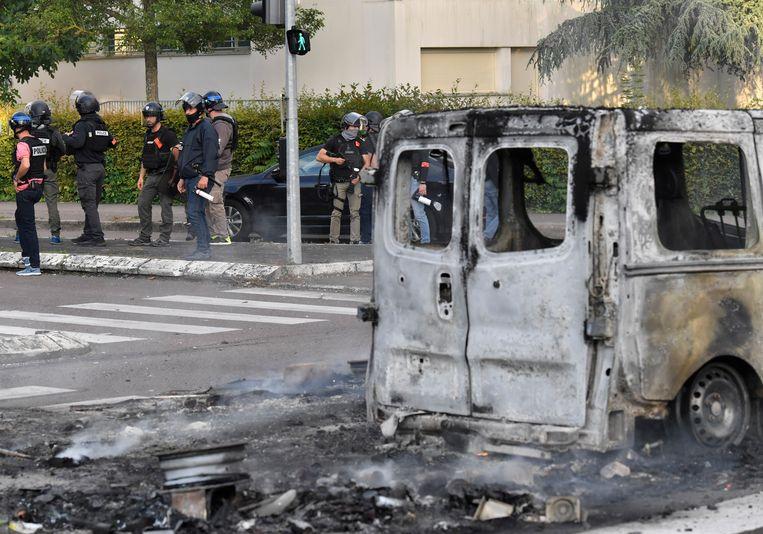 Het wrak van een busje dat in vlammen is opgegaan bij de gewelddadigheden in Dijon. Beeld AFP