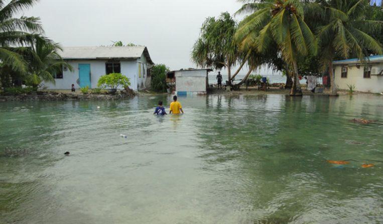 Twee lokale bewoners waden door het water van een overstroming die is veroorzaakt door de hoge zeespiegel Beeld Giff Johnson