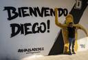 Een fan poseert bij een welkomstbord voor Diego Maradona.