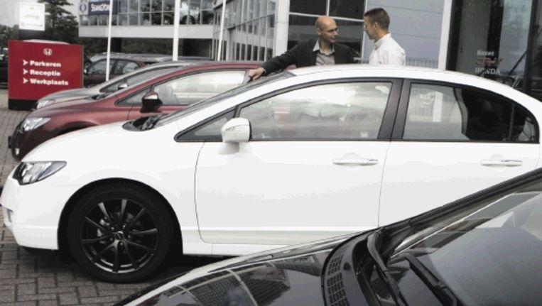 Een klant toont interesse voor de Honda Civic Hybrid bij een dealer in Amersfoort.  Beeld