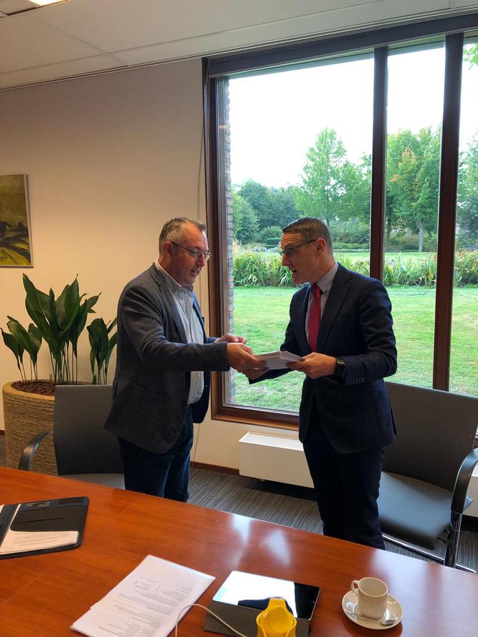 Johan van der Heijden (L) van Burgerinitiatief Behoud Gemeenschapshuizen voor Laarbeek reikt dinsdagmorgen de handtekeningen en een verklaring uit aan burgemeester Frank van der Meijden.