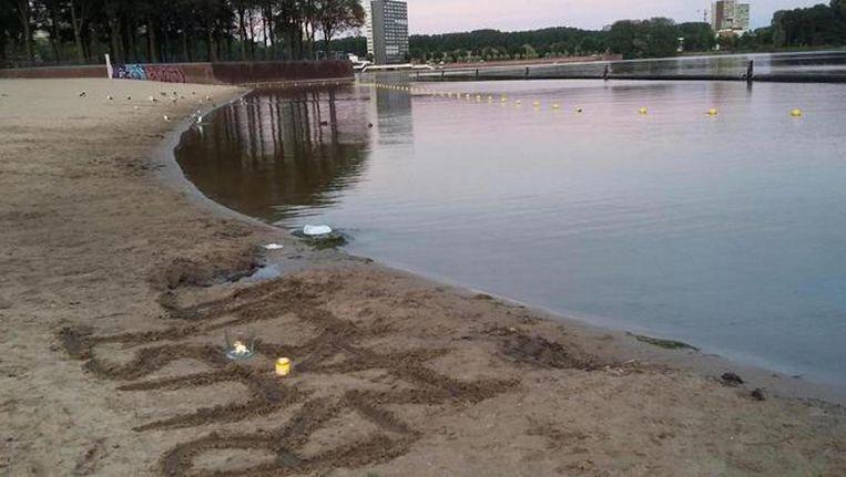 Een man heeft 'rust zacht' geschreven in het zand bij de Sloterplas. Beeld Hanneloes Pen