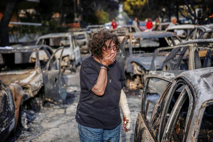 Een vrouw probeert haar hond te vinden in het dorp Mati, dat door de natuurbrand zwaar getroffen werd.