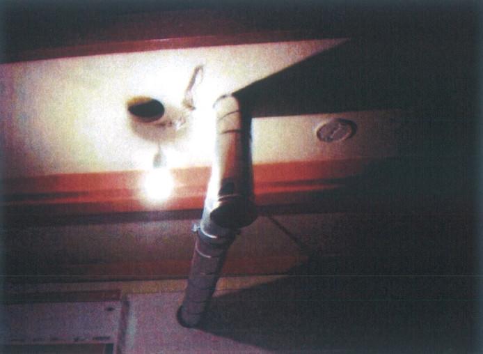 Doorvoer in brandvertragende wanden tussen kamers op de bovenverdieping, zoals gefotografeerd bij controlebezoek. De foto is opgenomen in het rapport dat de bezwarenzitting op tafel heeft.