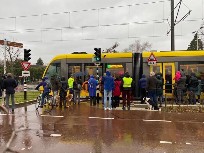 Actievoerders zien hoe de tram langs komt rijden, terwijl het verkeerslicht voor fietsers op groen staat.