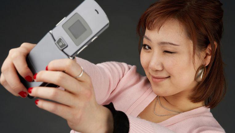 Een vrouw met een flip-phone Beeld null