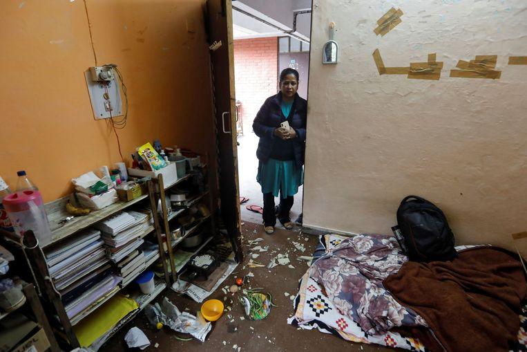 Een vrouw bekijkt de schade in de kamer van studenten aan de Jawaharlal Nehru University, na de aanval door een knokploeg. Beeld Reuters