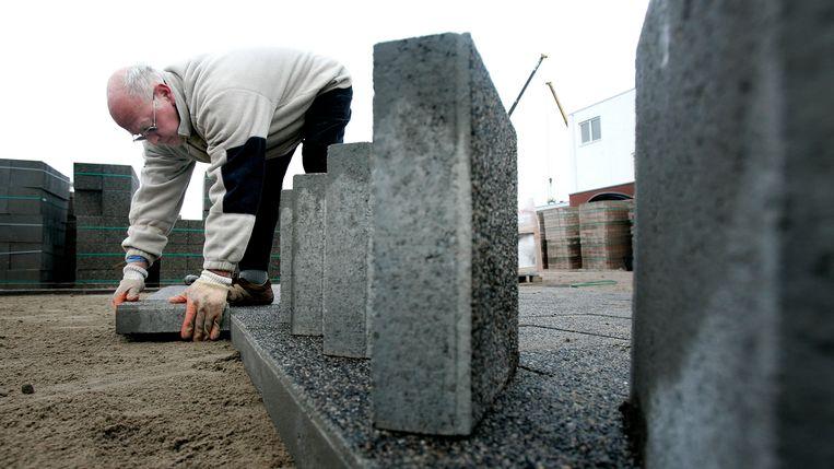 De 65 jarige Piet Hofman werkt als bestrater in Rotterdam. Beeld ANP XTRA