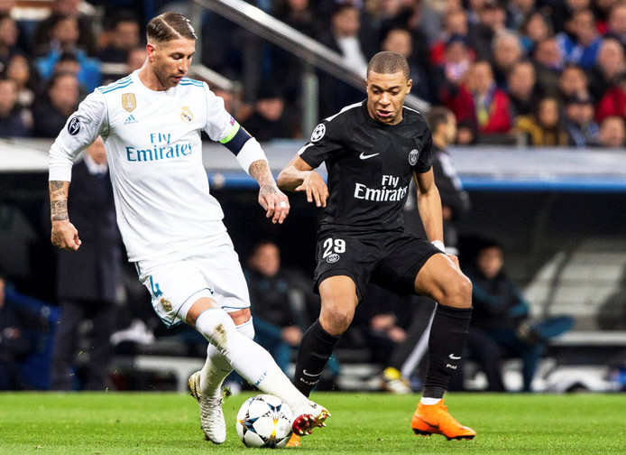 Sergio Ramos houdt Kylian Mbappé van de bal.