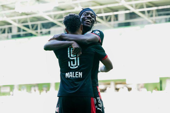 Donyell Malen en Noni Madueke vieren een goal van PSV in Groningen.
