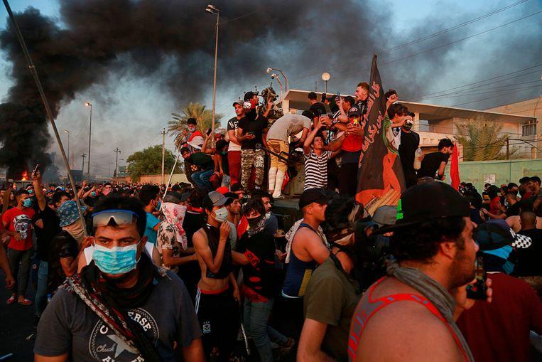 Demonstranten klimmen op een gepantserd voertuig en steken het in brand tijdens een betoging in Bagdad.  Beeld  AP