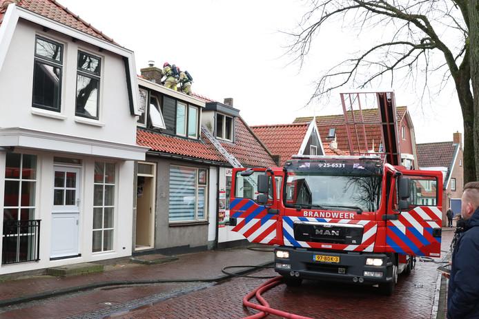 De brandweer ging het dak van pizzeria La Cassa op Urk op om goed bij de brandhaard te komen.