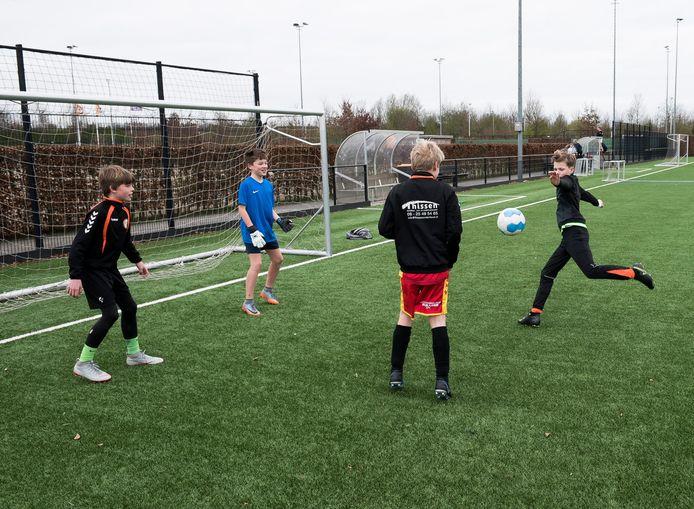 Jongens voetbalden, vorige week, op het lege veld van voetbalvereniging Desto in Utrecht. Vanaf volgende week mag dat ook officieel weer.  Maar wel met 1,5 meter afstand als je ouder dan 12 jaar bent.