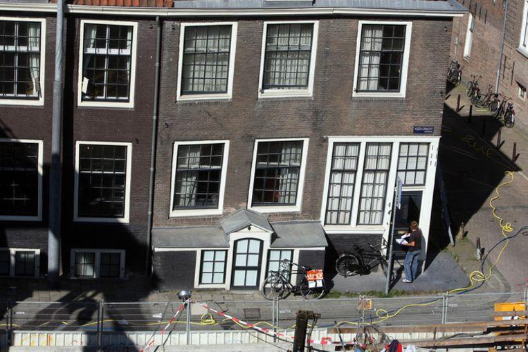 Een nietsvermoedende postbode brengt de post rond binnen de afzetting die de politie heeft neergezet rondom de woningen aan de Vijzelgracht die woensdagavond zijn verzakt. FOTO ANP/Evert Elzinga Beeld