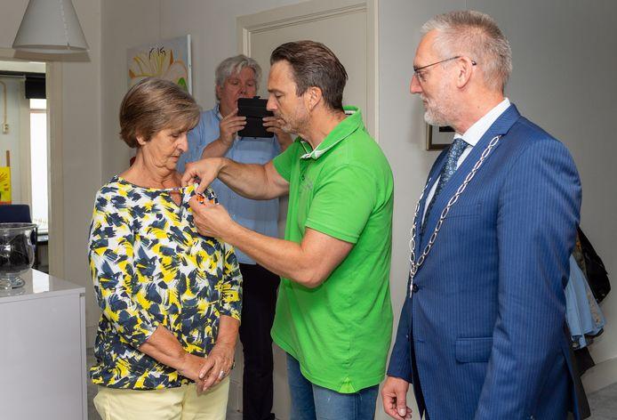 Zoon Ard decoreert Corrie van Bottenburg-Elsenga onder het toeziend oog van burgemeester Tom Horn.