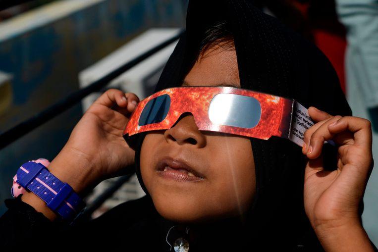 Een Indonesisch kind bekijkt de zonsverduistering in Banda Aceh.