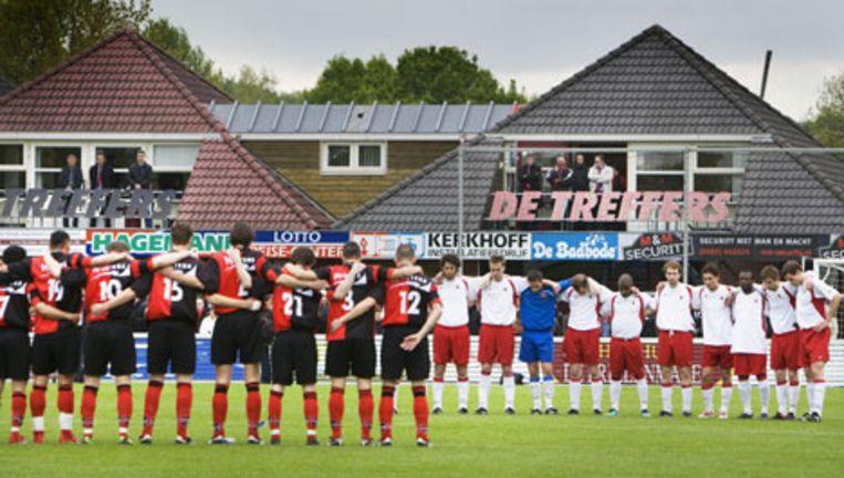 Voetballers van de Groesbeekse hoofdklasser De Treffers houden donderdag voorafgaand aan de titelstrijd tegen voetbalclub AFC (wit tenue) Amsterdam een minuut stilte ter nagedachtenis aan familieleden van een van de leden van de voetbalclub. Foto ANP Beeld
