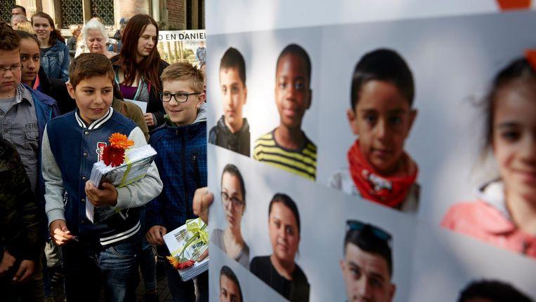 Kinderen overhandigen het fotoboekje Ik Blijf Hier aan Kamerleden. Het boekje is een oproep tot verblijfsrecht voor kinderen die al meer dan vijf jaar zonder verblijfsvergunning in Nederland wonen. Beeld anp