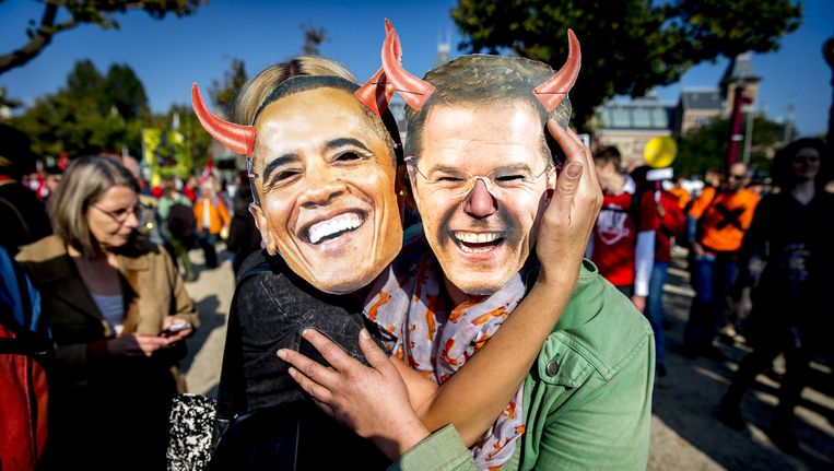 Deelnemers met maskers van Premier Rutte en president Obama tijdens een grote demonstratie tegen het omstreden handelsverdrag TTIP. Beeld anp