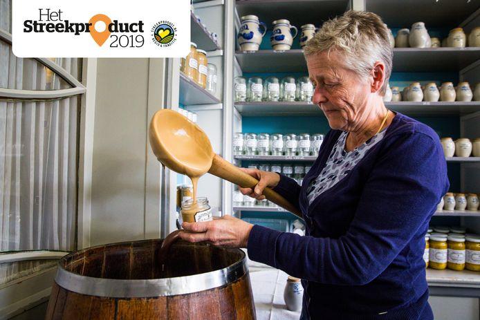 Catherine Caesens schept de artisanaal gemaakte mosterd in de winkel met een grote houten lepel in potjes.