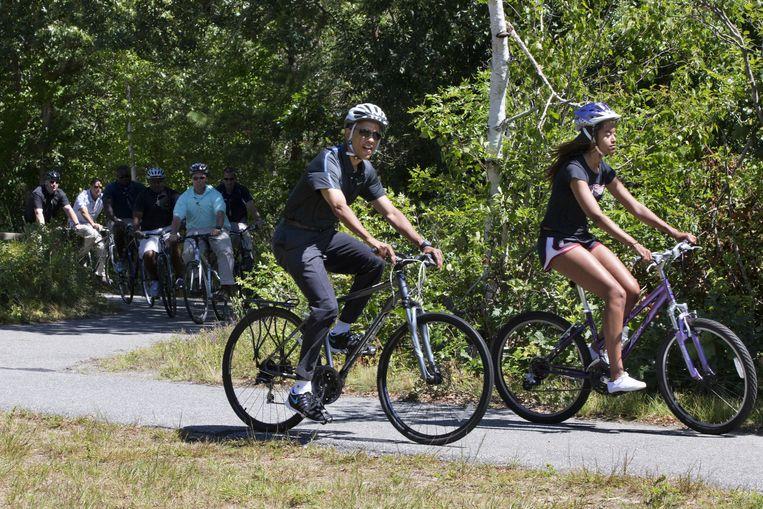 Barack Obama maakt tijdens zijn vakantie een fietstochtje met zijn dochter Malia, waarbij hij gevold wordt door beveiligers Beeld ap